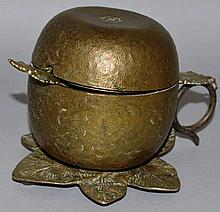 A GILDED APPLE JAM POT AND COVER with spoon on a l