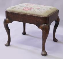 A GOOD GEORGE I WALNUT STOOL with drop-in needlework seat, supported on cabriole legs.
