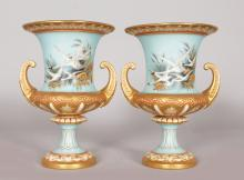 A SUPERB PAIR OF ROYAL WORCESTER CAMPAGNA VASES, painted with flying swans by CHARLES BALDWYN, Pattern No. 1926, the urn with rich gilt on a pale blue background. 7.5ins high.