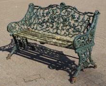 A GOOD GREEN PAINTED CAST IRON GARDEN BENCH of naturalistic form.