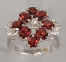 A SILVER, RUBY AND BRILLIANT SET CLUSTER RING.