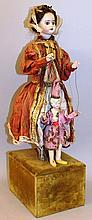 AN UNUSUAL FRENCH STANDING AUTOMATON PORCELAIN DOLL modelled in a period dress h