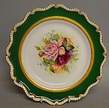 A ROYAL WORCESTER PLATE painted with roses inside an acid etched inner border an
