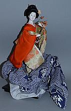 A CHINESE SEATED DOLL in a glass case.