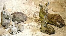 A PAIR OF GARDEN ORNAMENTS modelled as recumbent deer; together with a similar s