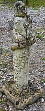 A RECONSTITUTED STONE GARDEN ORNAMENT modelled as a girl seated on a column.  2f