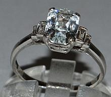 A GOOD WHITE SAPPHIRE AND DIAMOND RING set in platinum, baguette cut central whi