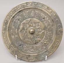 A CHINESE TANG STYLE SILVERED BRONZE MIRROR, decorated in relief with a ban
