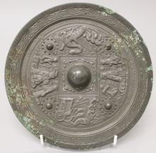 A CHINESE TANG STYLE BRONZE MIRROR, with encircling relief decoration of co