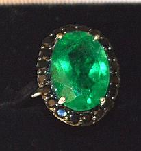 AN EMERALD AND BLACK GARNET DRESS RING.