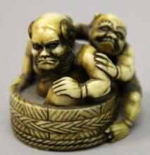 A JAPANESE STAINED IVORY NETSUKE OF TWO ONI