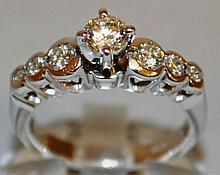 A SEVEN STONE DIAMOND RING, central stone flanked