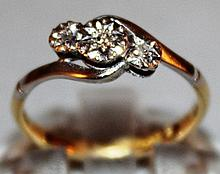 A THREE STONE DIAMOND CROSSOVER RING set in 18ct y