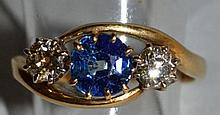 AN 18CT YELLOW GOLD CROSSOVER RING set with centra