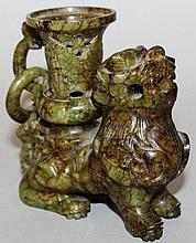 A CHINESE SPECKLED JADE DOG OF FOE CANDLESTICK wit