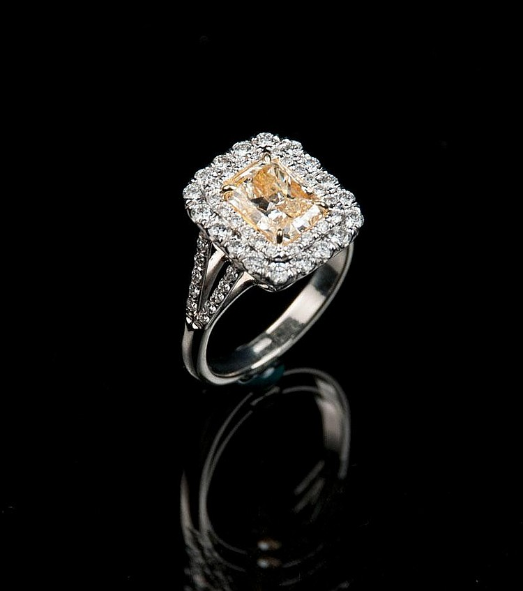 Platinum ring with one cut cornered rectangular modified brilliant fancy intense yellow diamond, approx. 2.02 cts. and 58 round brilliant cut diamonds, approx. 1.01 cts. with EGL USA Certificate # US 907093602D.