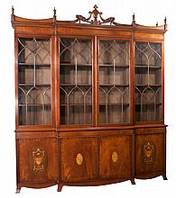 "Sheraton style mahogany breakfront bookcase with shaped pediment, urn carved crest, mullion glass doors, four doors in the base with satinwood urn and oval inlay in the doors, 96"" wide, 20"" deep, 109"" high"