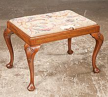"""Queen Anne style mahogany stool on cabriole legs with shell carved knees and pad feet with needlepoint cushion, c.1900, As Found, (label on stool reads Wolff, Godson and O'mera Ltd.) 27"""" long, 20"""" wide, 17.5"""" high"""