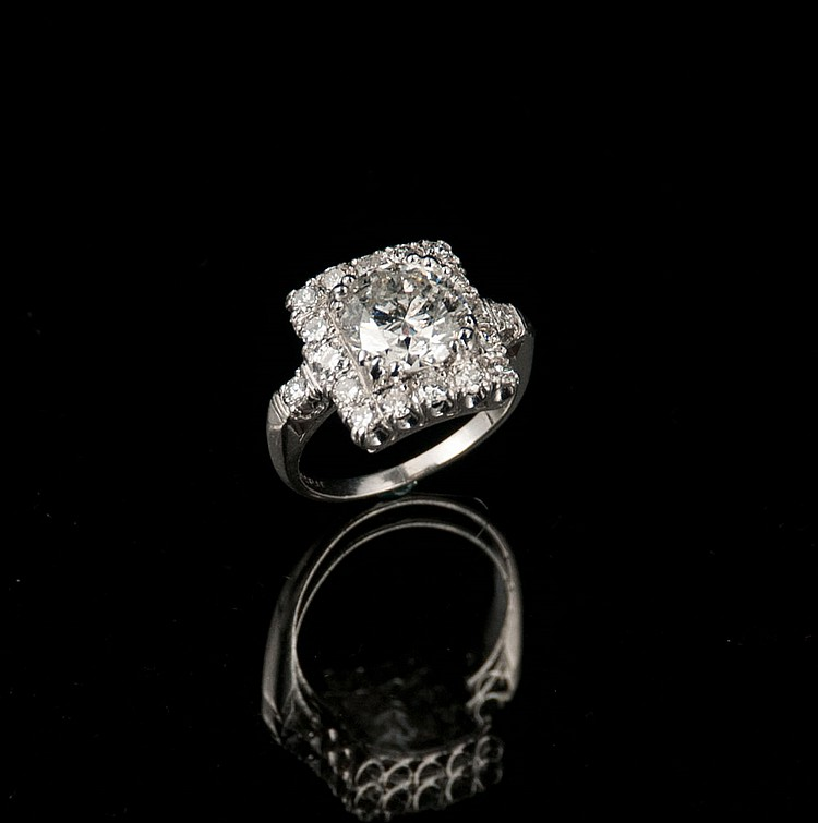 Platinum ring with round brilliant cut center diamond, approximately 3.02 cts., and surrounded by 18 round brilliant cut diamonds, approx. 4.02 cts.