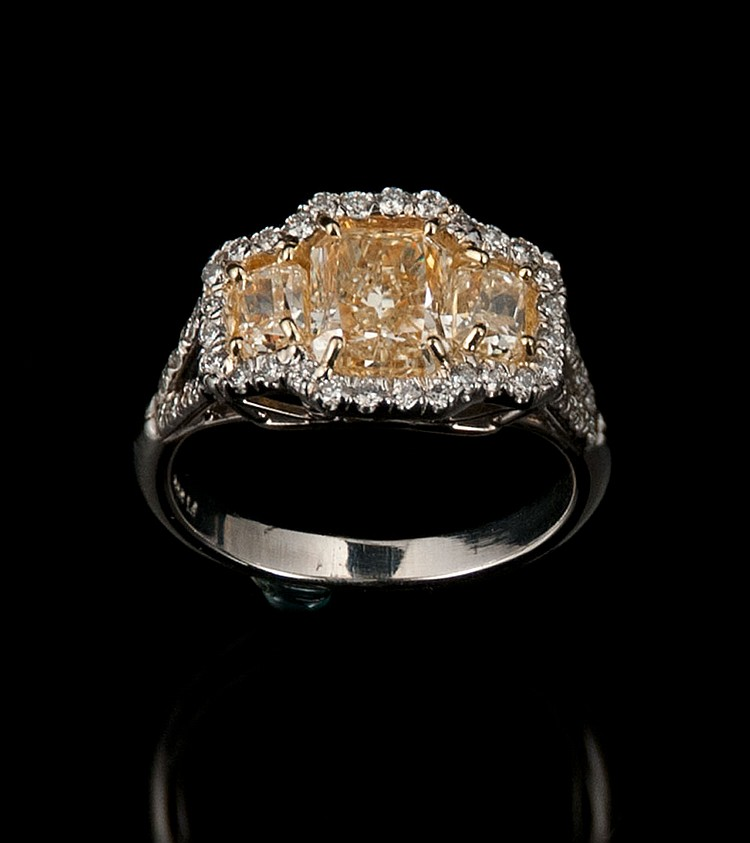 Platinum ring with one cut cornered rectangular modified brilliant fancy intense yellow diamond, approx. 2.05 cts. and two side cut cornered rectangular modified brilliant diamonds, approx. 0.86 cts., with EGL certificate US908819027D.