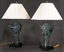 Pair of Neoclassic bronze patinated urn shaped lamps on three legs with rams heads terminating on hoof feet with silk shades, 33
