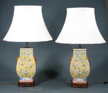 Pair of Chinese porcelain custom lamps with yellow, blue and green leaf and floral decoration, carved bases and shades, 27.5