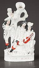 Staffordshire figure of a man and a lady holding a guitar and another man standing by a tree,