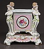 Square porcelain planter with figure each corner and floral decoration and on a footed platform base, 10