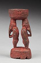 Mortier présentant deux ancêtres à bec d'oiseau plongeant. Bois, traces de colorant minéral ocre rouge.