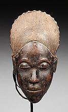 Masque de case sculpté d'un beau visage à l'expression sereine et agrémenté d'une coiffe dentelée en arc de cercle. Bois, ancienne patine d'usage brune et miel brillante, traces de colorant minéral blanc.