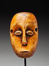Masque de grade présentant un visage à la belle expression juvénile, les yeux en grain de café sculptés en relief. Ivoire, ancienne patine d'usage miel et rousse.