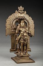 Figure votive présentant un cavalier (peut être une divinité guerrière) tenant un bouclier et une épée dans ses mains. A l'arrière, une arcature de temple. Laiton, fonte à la cire perdue, ancienne patine d'usage.