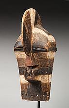 Masque de danse initiatique Kifwébé, de type masculin caractérisé par la crête sagittale. Ce masque présente des formes cubisantes rehaussées de colorants minéraux aux couleurs contrastées. Bois, crin de cheval, ancienne patine d'usage et