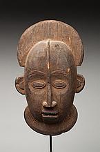 Masque de case présentant un visage à l'expression déterminée. Bois, patine d'usage brune.