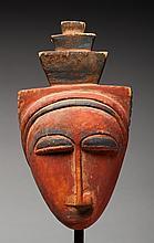 Masque diminutif de grade ou de case présentant un visage au nez longiligne surmonté d'une structure étagée. Bois léger avec rehauts de colorants minéraux, ancienne patine.