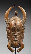 Masque de corporation Kpelié. Il présente un visage arborant les traits de plusieurs animaux totems comme le buffle, la chauve-souris et l'araignée entre autres. Cette œuvre est enrichie avec maitrise de nombreux décors filigranés et
