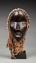 Masque de danse présentant un visage la bouche et les yeux grands ouverts, le front est agrémenté d'une couronne de cauris disposée en arc de cercle. Bois, ancienne patine d'usage, brune et miel, coton, cauris et matières organiques.