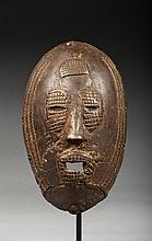 Masque de corporation ou de case, il présente un visage à l'expression affirmée, auréolé sur le pourtour de trois petites frises en relief. Laiton, réalisé par la fonte à la cire perdu, ancienne patine d'usage.