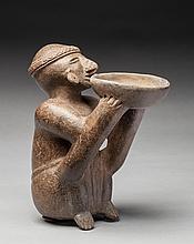 Rare statuette présentant un dignitaire assis tenant avec révérence une coupe à offrandes qu'il dirige vers le ciel. Belle expression intense et intériorisée du visage. Terre cuite brune et rouge café.
