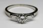 BAGUE SOLITAIRE en platine et or gris centrée d'un diamant de taille brillant d'environ 0,90 carat, épaulé par deux diamants de taille baguette. Poids brut: 4,1 g TDD: 63