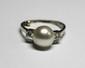 BAGUE en or gris ornée d'une perle blanche épaulée par deux diamants de taille brillant. Poids brut: 2,9 g TDD: 49,5