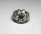 BAGUE en or gris ajouré stylisant une fleur, centrée d'un saphir rond de taille cabochon, les pétales formés de dix diamants de taille ancienne de forme poire. Poids brut: 8,7 g TDD: 59