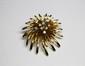 BROCHE en or jaune stylisant une fleur, ornée en son centre d'une succession de dix diamants de taille brillant réhaussés. Poids brut : 15,8 g