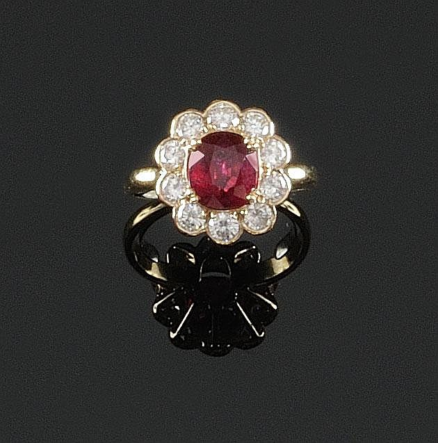 BAGUE en or jaune ornée en son centre d'un rubis de taille ovale de 2,34 carats dans un entourage de diamants de taille brillant. Poids brut : 5,4 g TDD : 56 -57 A RUBY, DIAMOND AND YELLOW GOLD RING