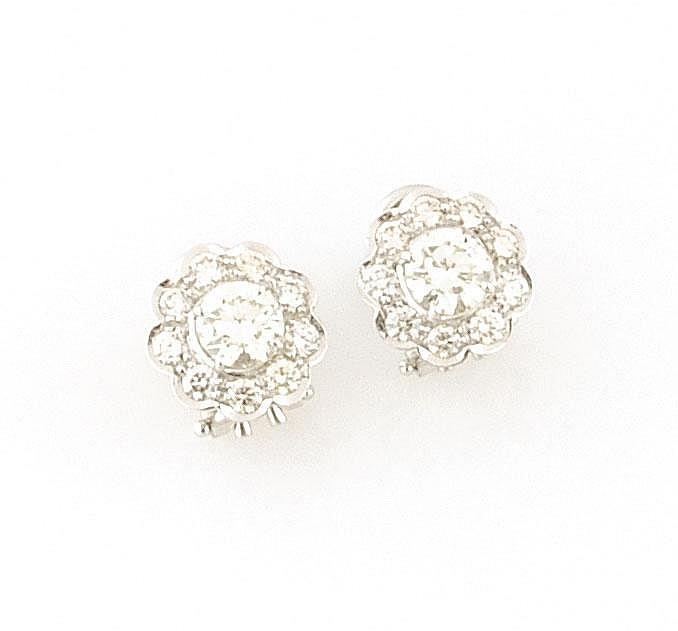 PAIRES DE BOUCLES D'OREILLES en gris stylisant une fleur retenant en son centre un diamant de taille brillant d'environ 0,70 carat dans un entourage de diamants de taille brillant. Poids brut : 5,6 g A DIAMOND AND WHITE GOLD PAIR OF EARRINGS