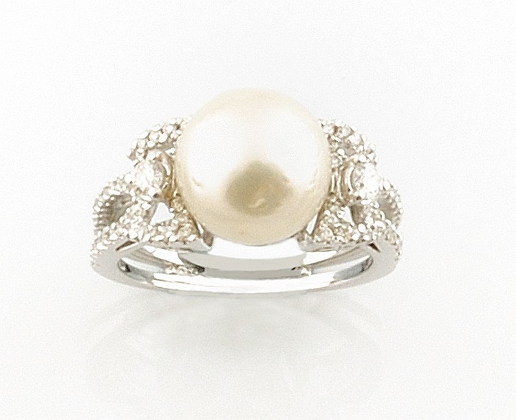 BAGUE en or gris retenant en son centre une perle de culture épaulée de deux diamants de taille brillant,  la monture finement ajourée,  pavée de diamants brillantés. Poids brut : 7,6 g TDD : 54 - 55 A PEARL, DIAMOND AND WHITE GOLD RING