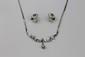DEMI PARURE en or gris, composée d'un collier et d'une paire de boucles d'oreilles, ponctuée de diamants stylisant des enroulements. Poids brut : 18,1 g