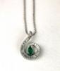 PENDENTIF or gris stylisant une volute pavée de diamants taille baguette, retenant en son centre une emeraude taillée en  poire en pampille. Poids brut: 9,4 g. hauteur: 3,3 cm