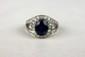 BAGUE en or gris ornée d'un saphir de taille ovale dans un entourage de diamants taille brillant formant une volute. Poids brut: 7,1 g. TDD: 52.