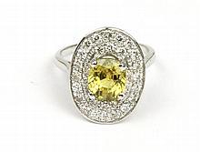 Bague en or gris ornée d'un saphir jaune de  4 carats environ Dans un entourage de diamants de taille brillant Poids brut : 5,9 g TDD : 53